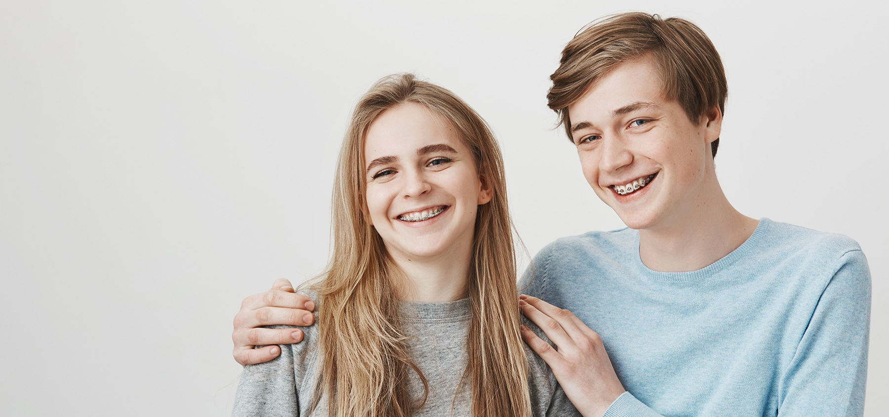 Two teens with braces smiling