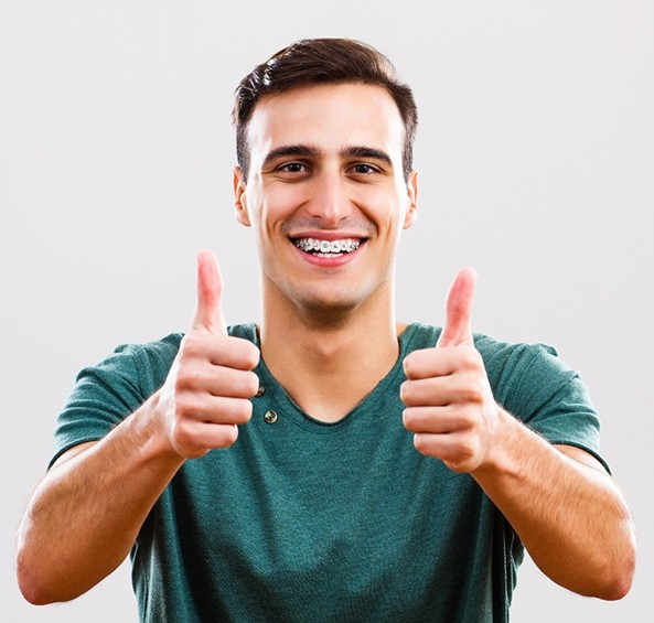 Male with braces for teens in Frisco with thumbs up